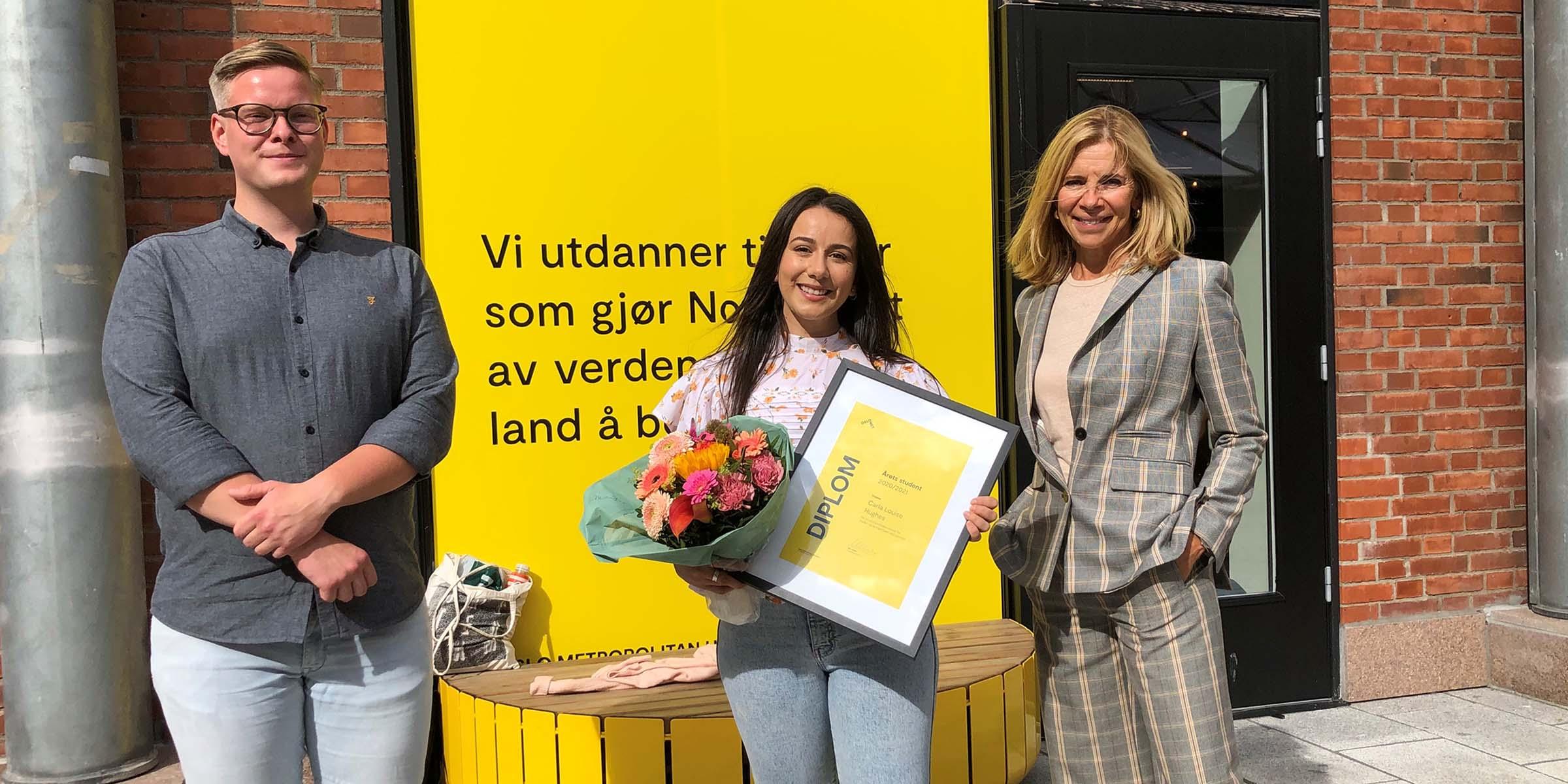 Carla Luise Hughes sammen med Rolf Martin Aspenes og Nina Waaler foran en gul vegg på OsloMet